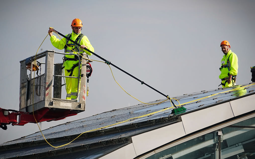 workmen cleaning solar panels